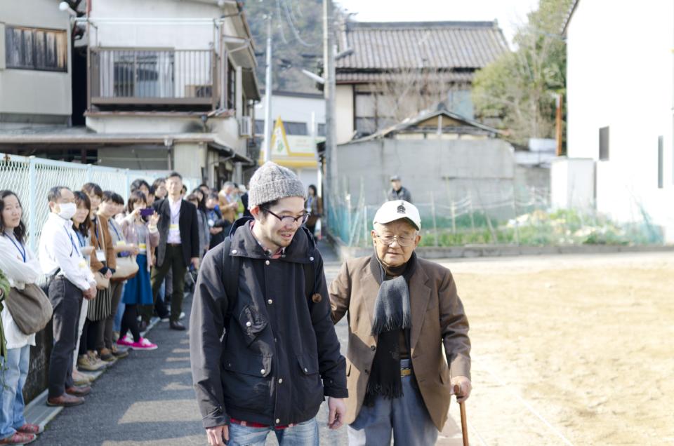 (写真について)街頭演劇の手法を取り入れた第1作『認知症徘徊演劇「よみちにひはくれない」』より。主演の岡田忠雄さん(右)と。