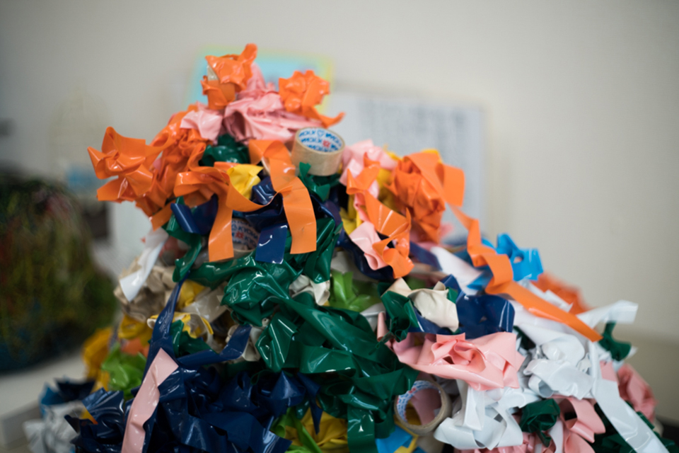 (写真について)何色ものビニールテープをぐるぐる重ねる緑川悠貴さんの作品。