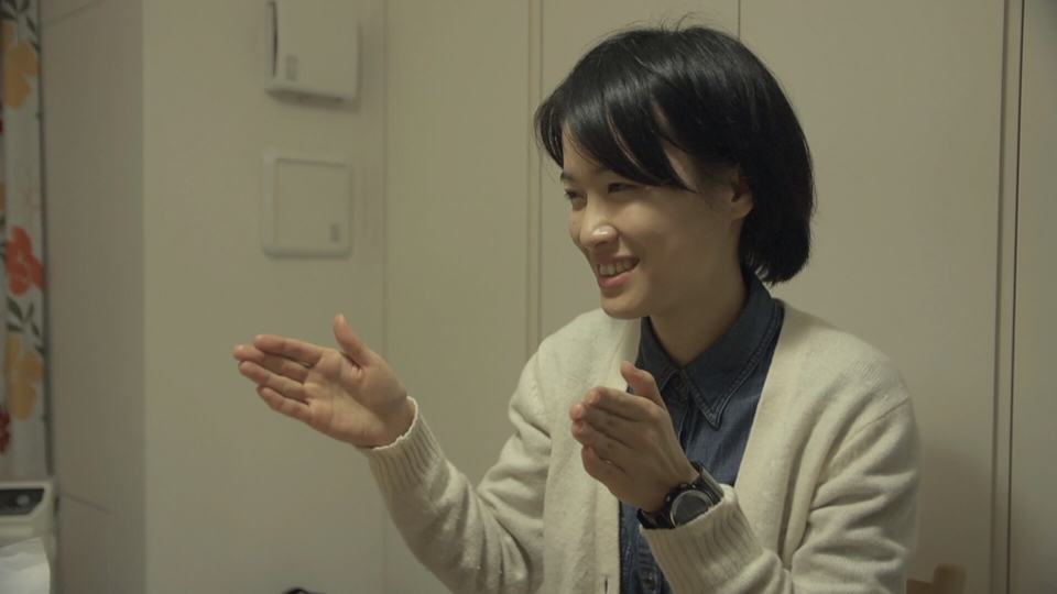(写真について)『もうろうをいきる』より。一般企業の人事部で働く川口智子さん。先天ろうで目にも弱視と視野狭窄がありながら、好きな能などの古典芸能にまつわる本を読み感想を書き記している。