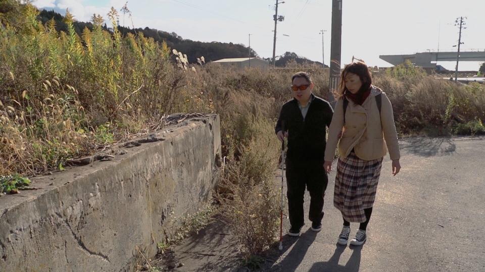 (写真について)『もうろうをいきる』より。小山賢一さんが地元・石巻にて、被災前の街の風景を説明するシーン。