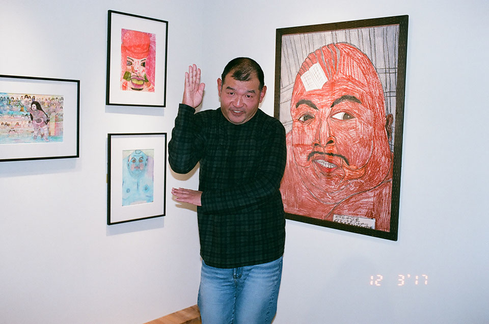 (About the photo)Aoki poses as his favorite pro wrestler Abdullah the Butcher in front of his drawing of Butcher.