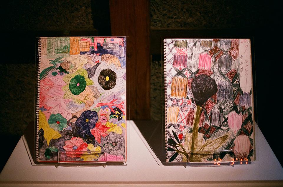 (写真について)「青木尊と花と女子」より、青木さんがスケッチブックに描く花は、そのままテキスタイルにもできそうな鮮やかさだ