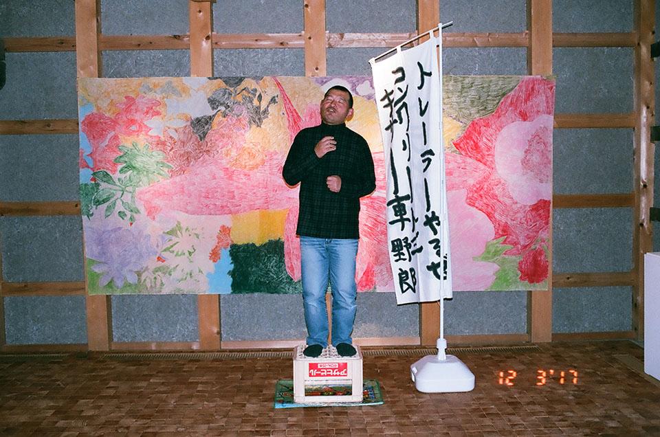 (写真について)布にクレヨンと鉛筆で花が描かれた作品の前でリサイタルが始まった。歌謡曲のメドレーを熱唱する青木さん
