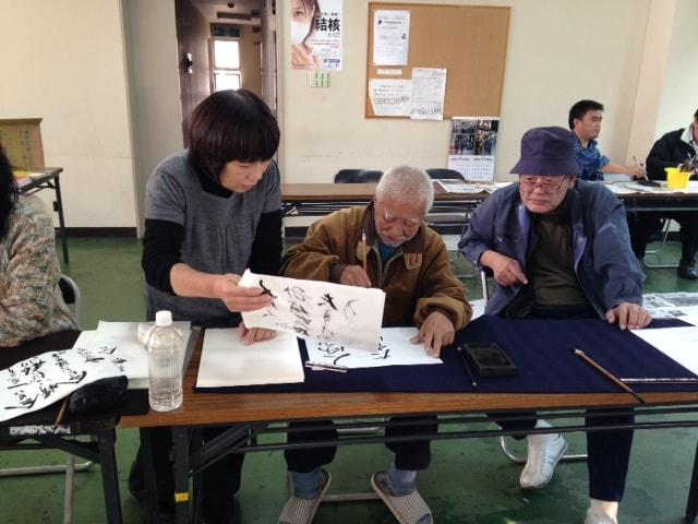 (写真について)「ココルーム」が主催する市民大学「釜ヶ崎芸術大学」の書道講座の様子。