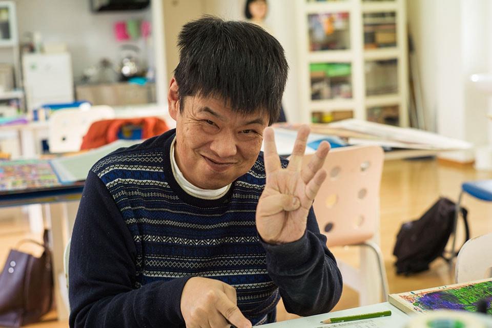 (写真について)穴瀬生司さんは絵を描いたり、電子基板を取り付けた木を削っていた。終始スマイリー。