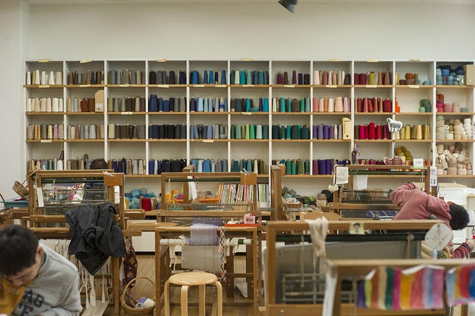 (写真について)手織りと染めを行うスタジオ。ここでメンバー自身が織りたいイメージの糸を選び、布を織り、 ショールや雑貨に仕立てている。棚には地域の人が無償で提供してくれた色とりどりの糸が並ぶ。