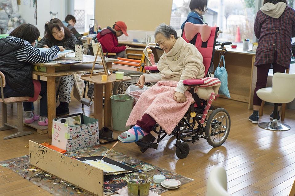 (写真について)上野和子さんは、左足で絵筆を軽やかに滑らせながら作品を描く。笑顔がチャーミングな〈HANA〉の最年長メンバー。
