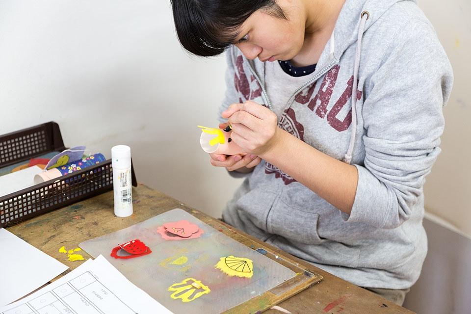 (写真について)この日の課題は「吊るし雛」。トイレットペーパーの芯に目を描き、装飾をしていく。