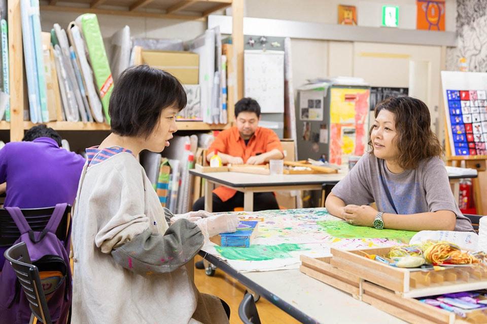 (写真について)2000年から絵画などを教えるボランティアとして〈西淡路希望の家〉に関わるようになり、現在は職員として美術部を担当する金武啓子さん(写真右)。