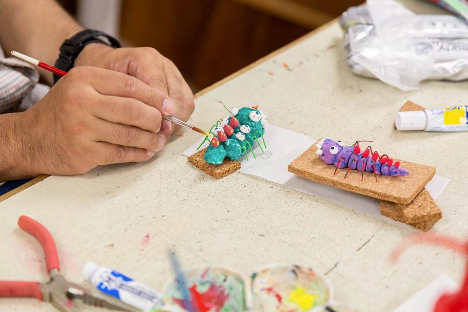 (写真について)藤戸修身(ふじと・おさみ)さんが手掛ける、ポップな伝統工芸のような粘土作品。机には完成品がいくつも並べられていた。