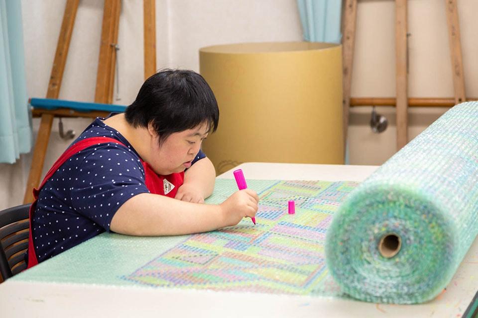 (写真について)一つひとつに丁寧に色を塗る東本憲子(ひがしもと・のりこ)さんのプチプチロールアート。ポコラートでも入賞。