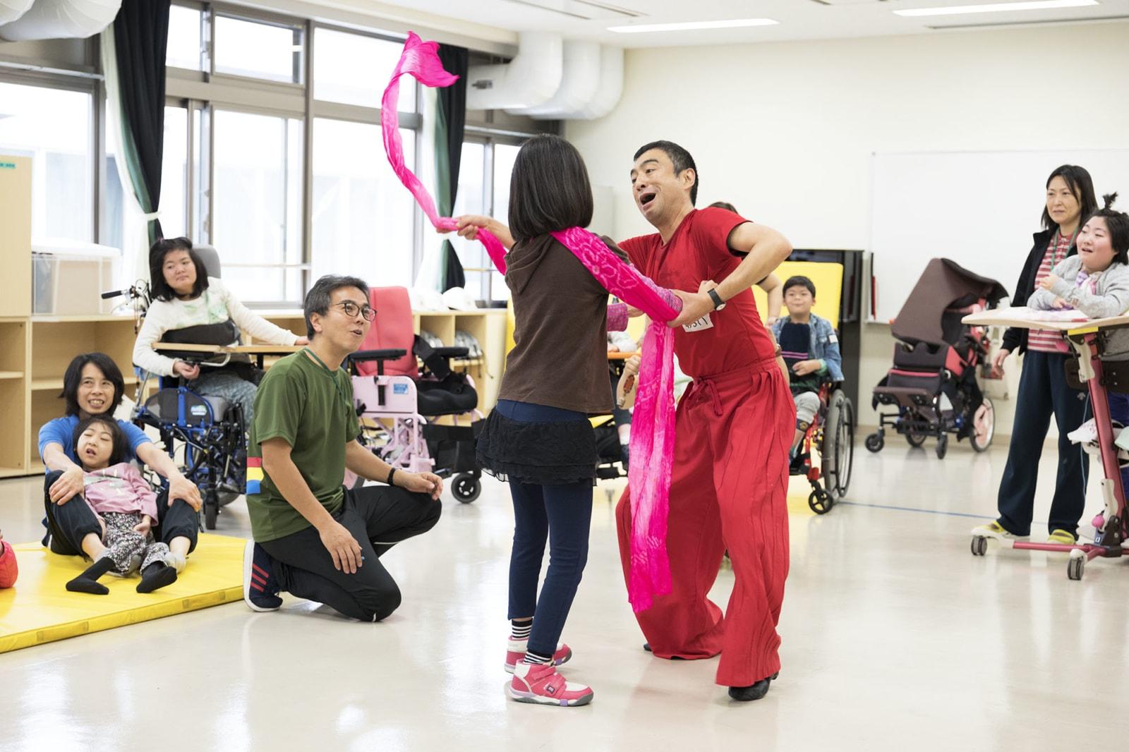 赤い服を着た、ダンサーの新井英夫さんが、鹿本学園の子どもと体を動かしています。