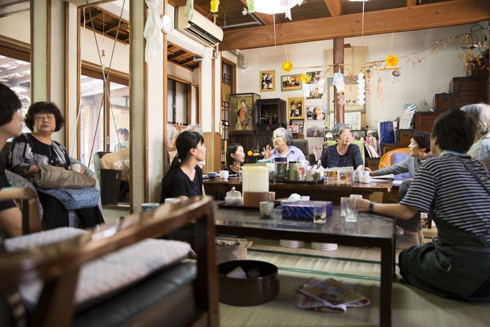 (写真について)〈宅老所よりあい〉。1991年、社会から孤立していた当時92歳の女性のため、福岡市中央区に開所した。1995年には〈第二宅老所よりあい〉を開設。両施設とも民家を改装し、現在は十数名ほどの利用者が通う。そして2015年、26名の利用者と特別養護老人ホーム〈よりあいの森〉をスタート。書籍『へろへろ−−雑誌『ヨレヨレ』と「宅老所よりあい」の人々』(鹿子裕文著、ナナロク社、2015年)の舞台にもなった。