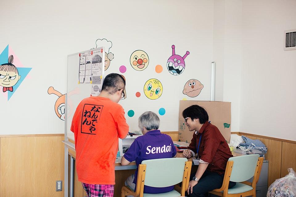 (写真について)塗さんの体調や様子を見ながら、日々制作のサポートをしている土谷康司さん(右隣)。