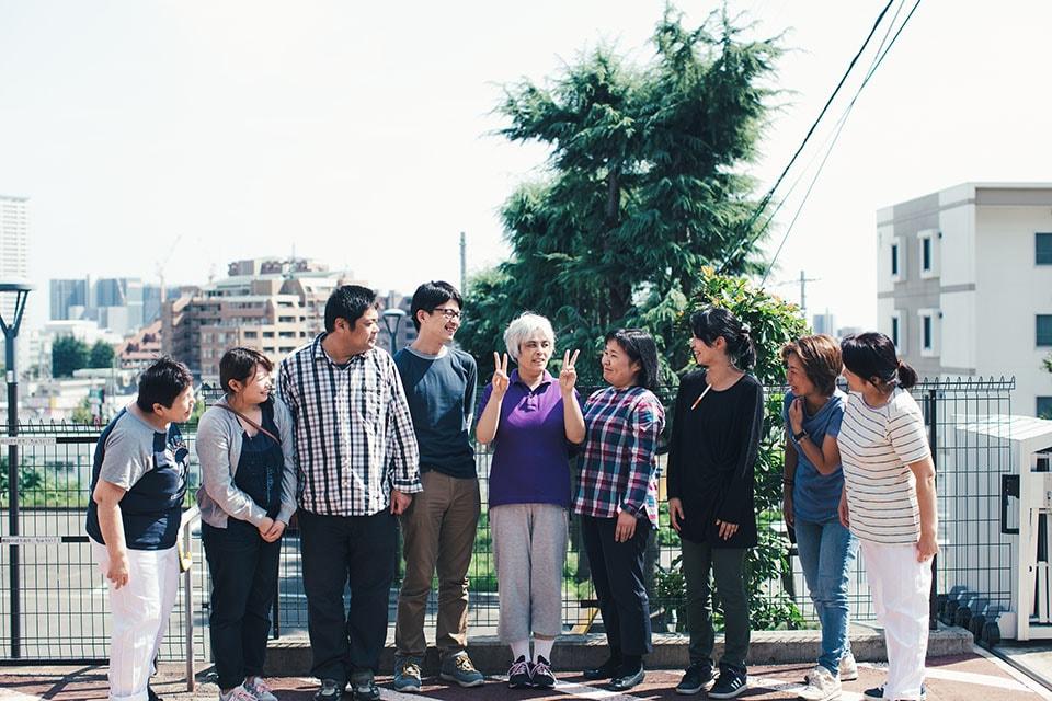 (写真について)施設長の渡部きみ江さん(塗さんの右隣)をはじめ、いつも塗さんを見守る事業所のみなさんと記念撮影。
