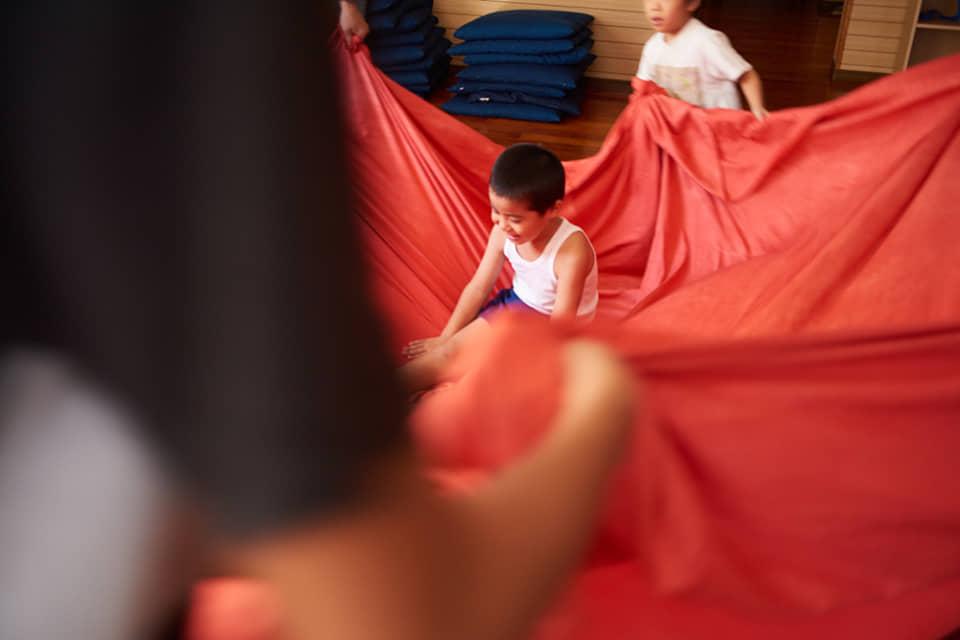 (写真について)名護市字宇茂佐の〈Atelier みるく やんばる〉での活動の様子。大きくて柔らかい布と戯れる「布あそび」は定番のプログラム。