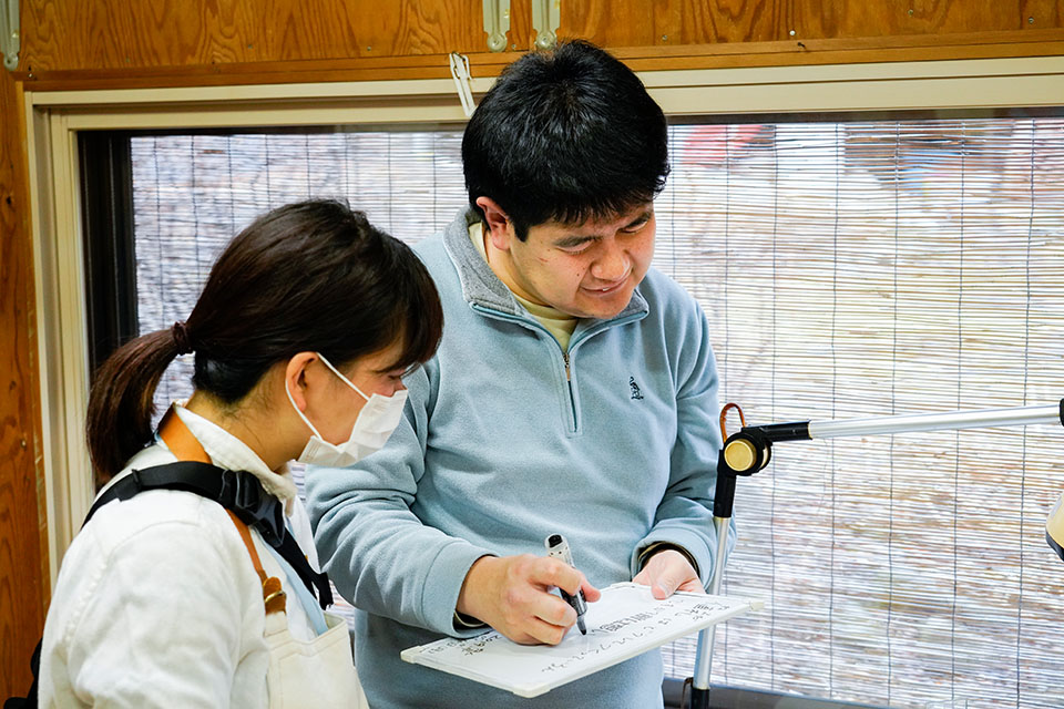 (写真について)周囲の音に敏感だと言う清水さん。支援員とのやりとりも筆談を基本としている。