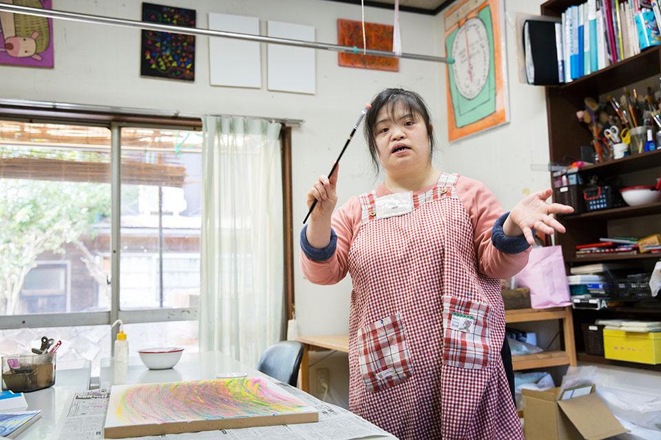 (写真について)童謡「たき火」を歌いながら、筆をタクトのように振る萌子さん。
