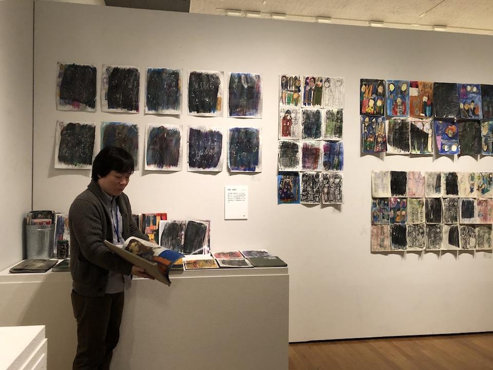 (写真について)朝地信介氏の解説。田湯加那子作品の前で。