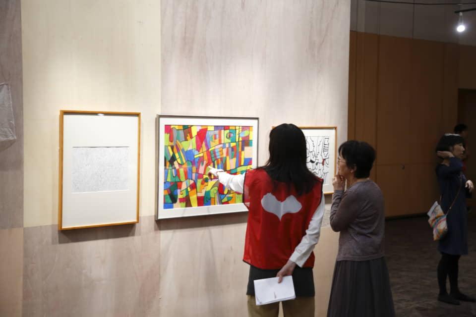 (写真について)小林覚の作品解説をするボランティアスタッフ