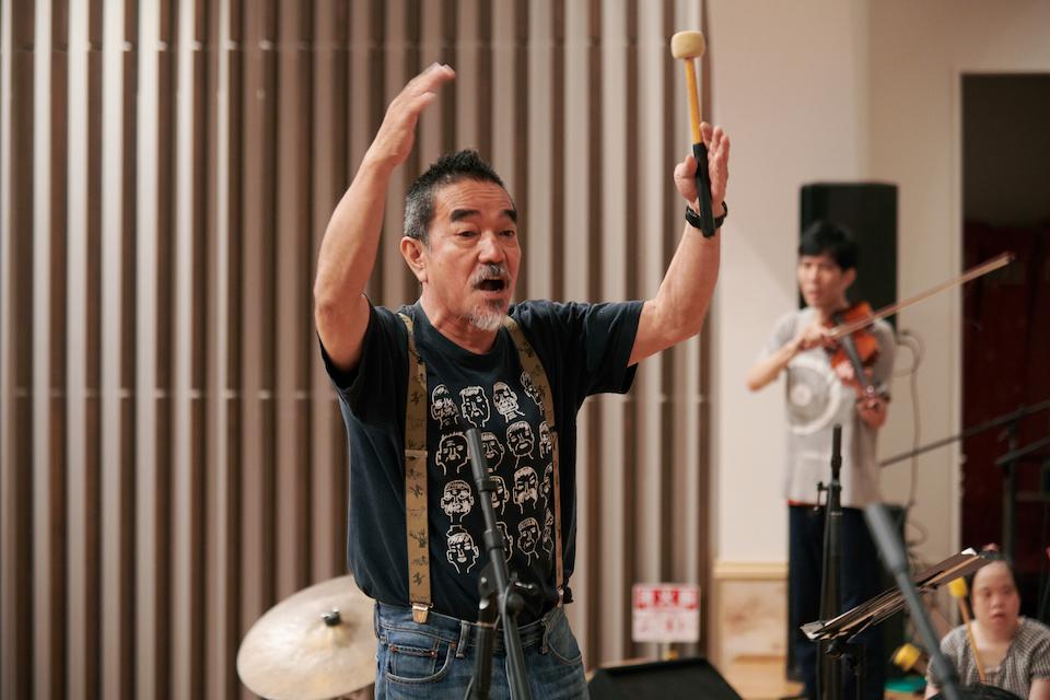 """(写真について)会話をするかのように音を紡いでいく「otto & orabu」指揮者/〈しょうぶ学園〉統括施設長、福森伸さん。「僕らの""""正解""""って、エナジーが来たときのこと。エナジーは激しいばかりじゃない。小さい音でも、ハートが来たときがいいの」。"""