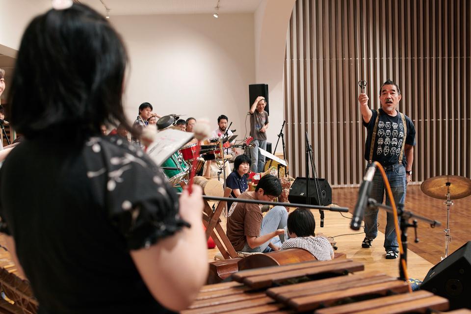 (写真について)曲の練習の合間には名前当てゲームや手品が行われ、みんなの集中力を高めていく。