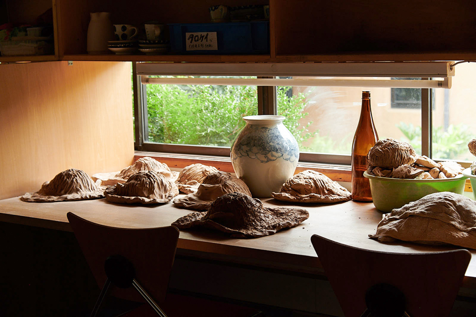 (About the photo)Unoki's desk at the Ceramic Workshop. Inside a bucket are many of her daily artworks. The glass bottle is for making shapes.