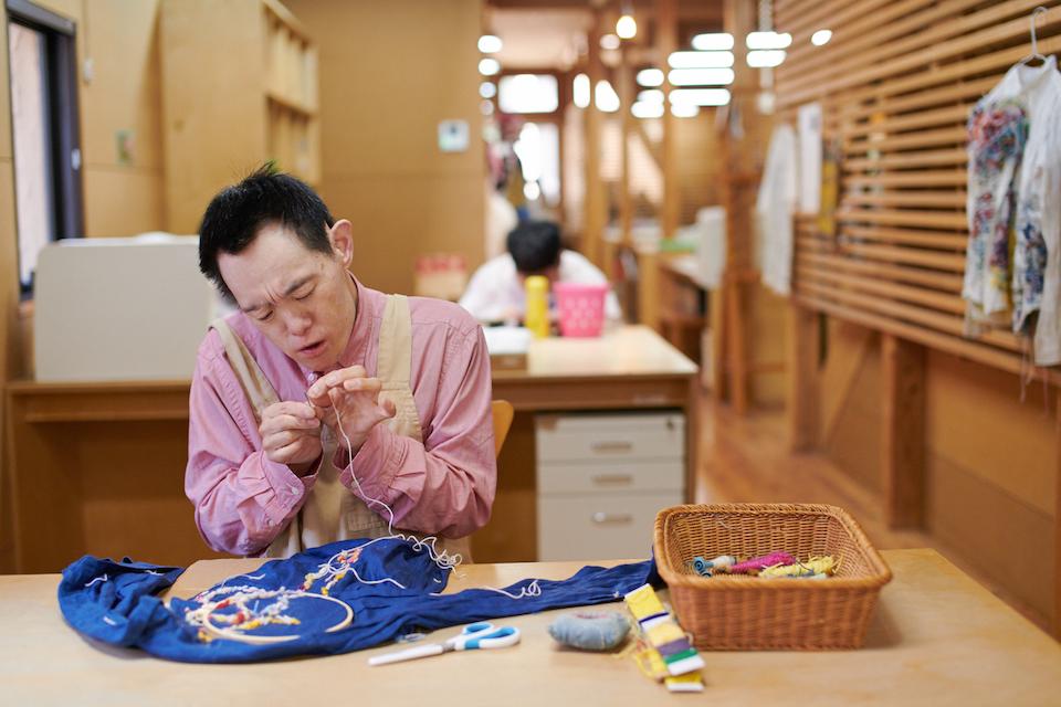 (写真について)針に毛糸をとおす勉さん。