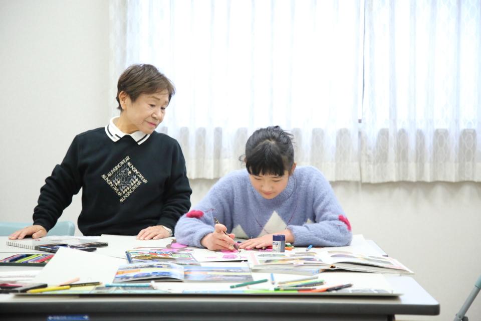 (写真について)谷澤佐規子先生に見守られながら、絵を描いていく。時々、先生からはアドバイスも。