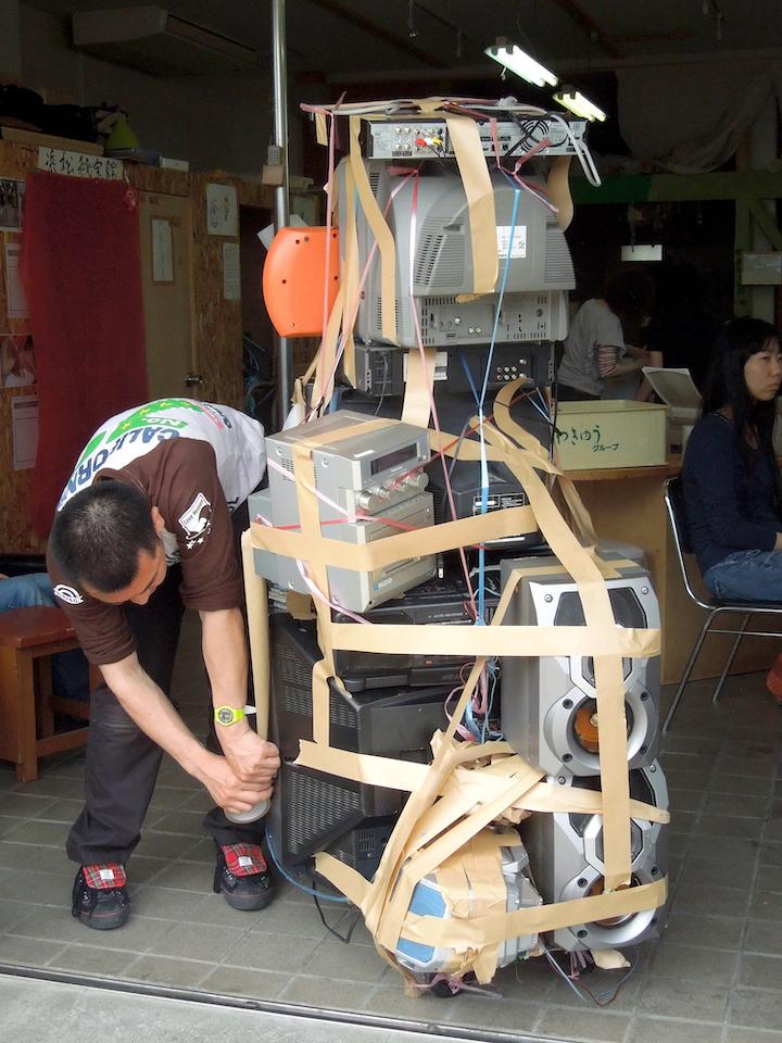 (写真について)尾形和記さんが大好きな電化製品を気持ちのままに積み上げたオガ台車。