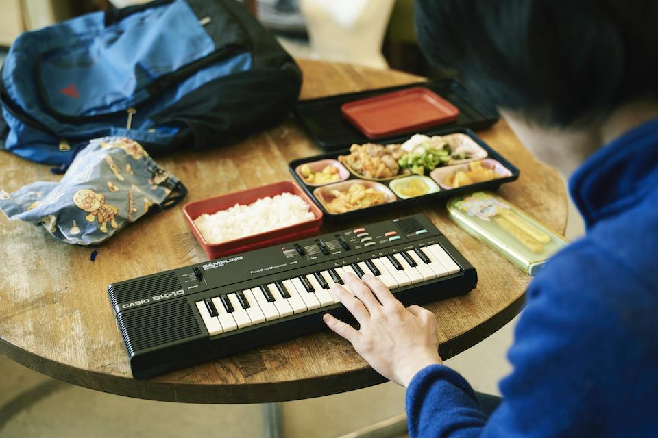 (写真について)朝からキーボードのリズムトラックを聴き続けるナカムラシュンスケさんは、食事のときも、散歩のときもキーボードを手放さない。