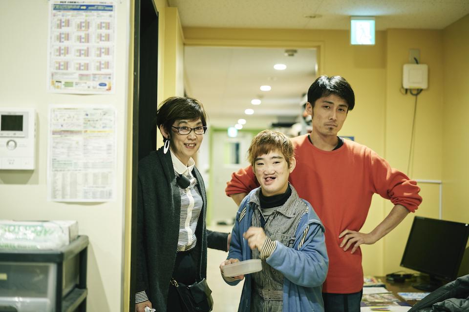 (写真について)久保田翠さんと息子の壮さん、職員のササキユーイチさん。23歳になった壮さんの未来を考えて、福祉の枠組みではなく、シェアハウスで共生する「実験」も始まっている。