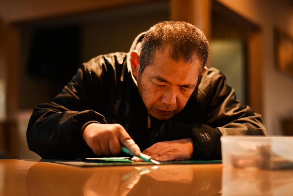 (写真について)版画制作を行う小室弘行さん。一心不乱にゴム版を彫り進める。