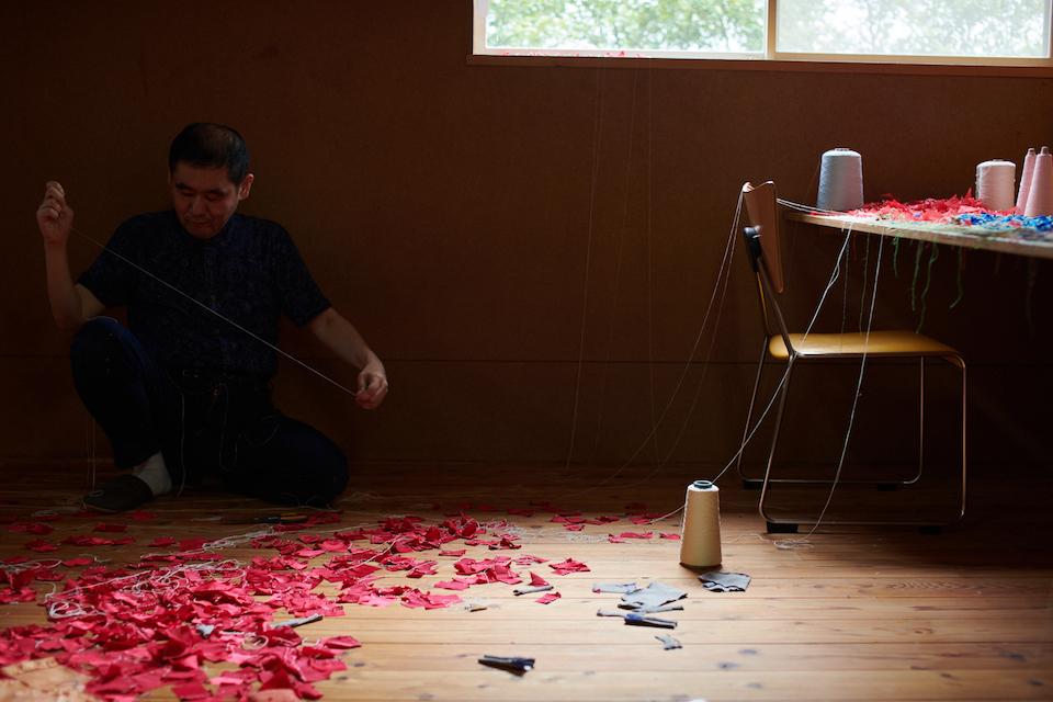 (写真について)細長い部屋でひとり、真紅の小さな布に糸を通す吉本篤史さん。