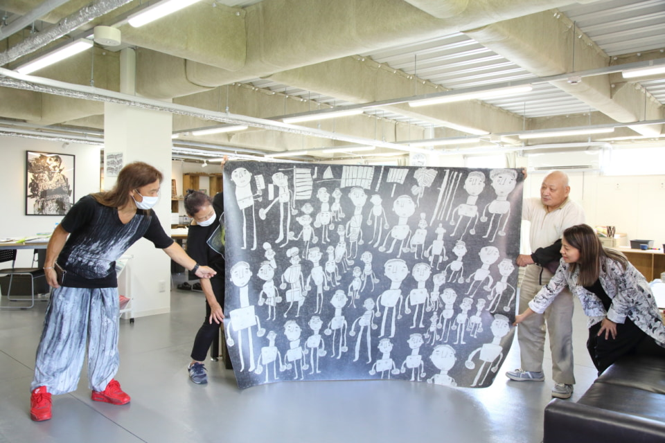(写真について)井上さんが巨大な作品を見せてくれた。左端にいるのが施設長の山下さん。