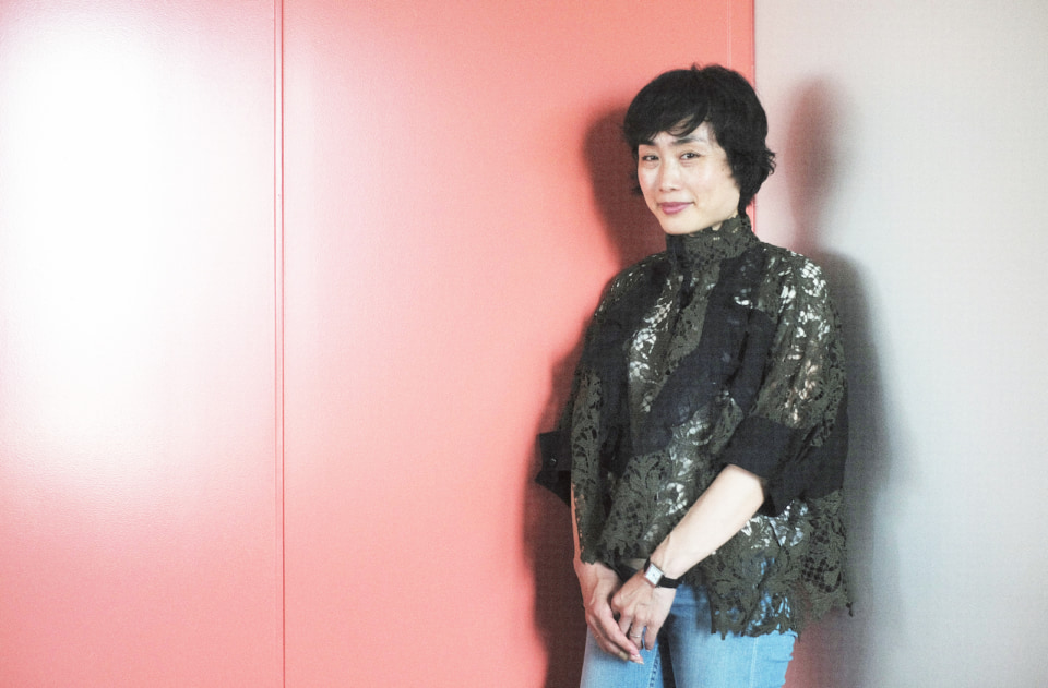 壁際でこちらを見つめる伊藤亜紗さん。